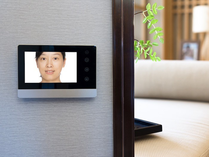 A room with wall-mounted video doorbell screen.